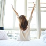 Young woman stretching her back in bed looking out over the sunrise